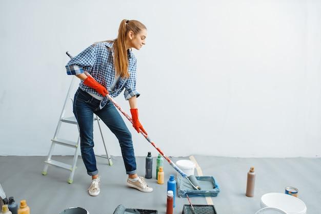 Malerin mit farbroller. hausreparatur, lachende frau bei der renovierung der wohnung, renovierung der zimmerdekoration