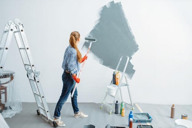 Malerin mit rolle malt wand. hausreparatur, lachende frau bei der renovierung der wohnung, renovierung der zimmerdekoration