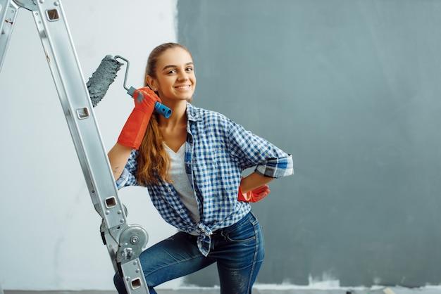 Malerin mit rolle malt wand in grauer farbe. hausreparatur, lachende frau bei der renovierung der wohnung, renovierung der zimmerdekoration