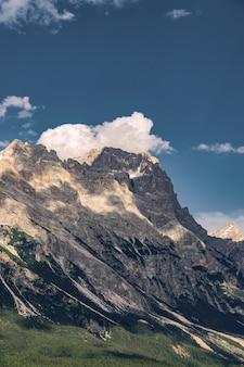 Malerische alpen mit felsigem berg unter blauem himmel