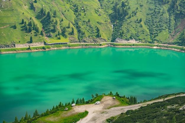 Malerische alpen mit see und grünem hügel