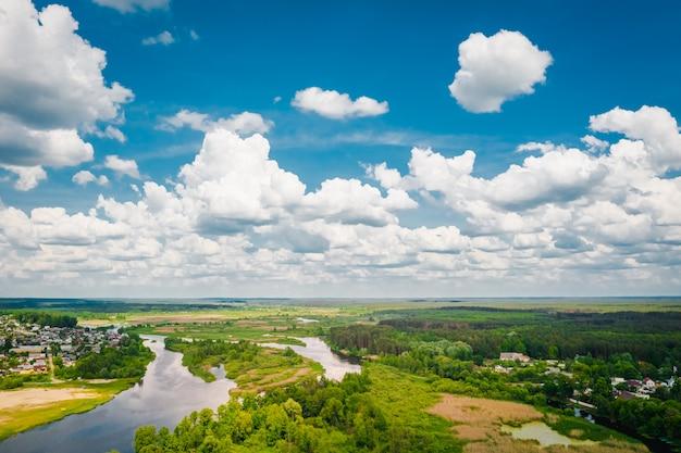 Malerische belarussische natur mit einem fluss, wald und wolken auf einem blauen himmel