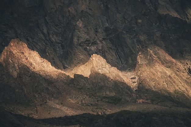Malerische berglandschaft mit felsen im goldenen sonnenlicht. naturhintergrund der felsigen bergwand mit scharfen felsen im goldenen sonnenschein. bunte sonnige kulisse mit hohem felsigem berg mit spitzen felsen