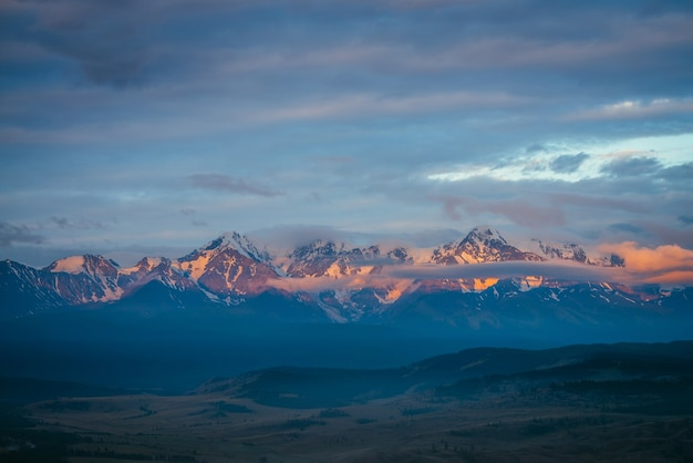 Malerische berglandschaft mit großer schneebedeckter bergkette, die von orangefarbener morgensonne unter niedrigen wolken beleuchtet wird. fantastische alpine landschaft mit schneebedecktem hochgebirgsrücken unter blauem bewölktem himmel bei sonnenuntergang oder bei sonnenaufgang.