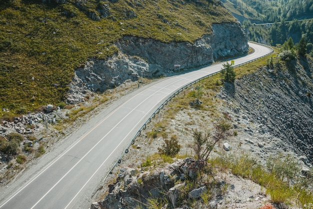 Malerische landschaft mit autobahn durch gebirgspass. seitenansicht zum trakt im hochland. schöne landschaft mit asphaltstraße mit fahrbahnmarkierungen. blick von oben auf die autobahn mit durchgezogener linie und felsigen bergen.