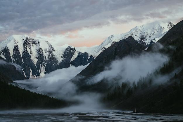 Malerische landschaft mit großen schneebedeckten bergen bei sonnenuntergang und dichten niedrigen wolken im bergtal mit waldsilhouette. atmosphärische landschaft mit hohen schneebedeckten bergen bei sonnenaufgang und dicken niedrigen wolken