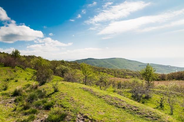 Malerische landschaft, regenwolken, mit grünen pflanzen bedeckte berge, landstraße verläuft zwischen hügeln