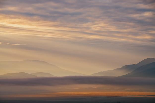Malerische morgendämmerung berglandschaft mit goldenen niedrigen wolken im tal zwischen bergsilhouetten unter bewölktem himmel. lebendige sonnenuntergangs- oder sonnenaufgangslandschaft mit niedrigen wolken im bergtal in leuchtender farbe.