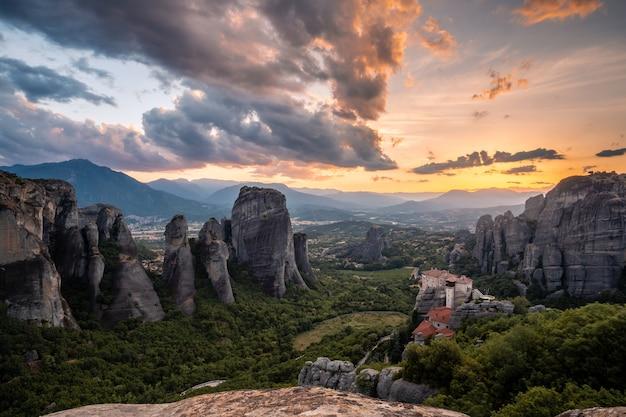 Malerische sonnenuntergangslandschaft eines breiten bergtals in griechenland mit bizarren klippen, einem dichten wald am fuße der berge und einem kleinen christlichen kloster auf einer klippe