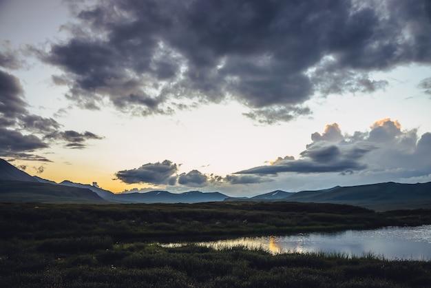Malerische sonnenuntergangslandschaft mit see unter lebendigem orangefarbenem steigungshimmel. bunte bergsonnenaufgangslandschaft mit leuchtender farbe bei bewölktem himmel und goldener reflexion auf dem see. wolken im morgengrauen mit farbverlauf.