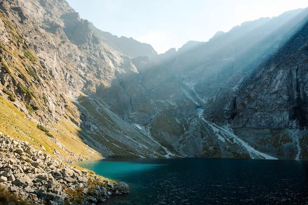 Malerischer blick auf den see morskie oko mit grünem wasser mit felsigen bergen und morgensonne