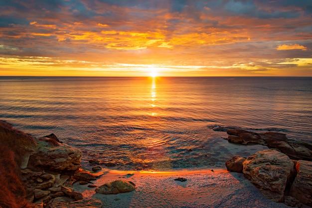 Malerischer sonnenaufgang über einem felsigen strand.