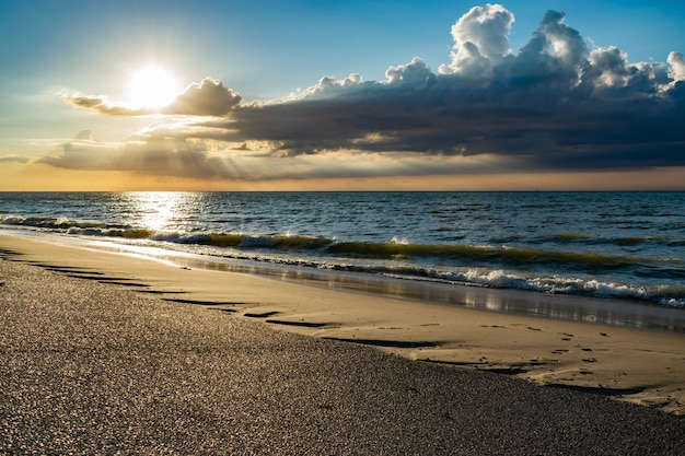 Malerischer sonnenuntergang am meer mit sonnenstrahlen und dunklen wolken über der nordsee.