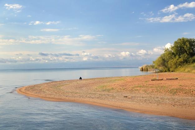 Malerisches sandiges seeufer mit blauem himmel und wolken an einem sommertag.