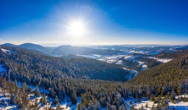 Malerisches winterpanorama der mit schnee und tannen bedeckten berghügel an einem sonnigen, klaren tag mit sonne und blauem himmel. unberührtes naturschönheitskonzept. exemplar