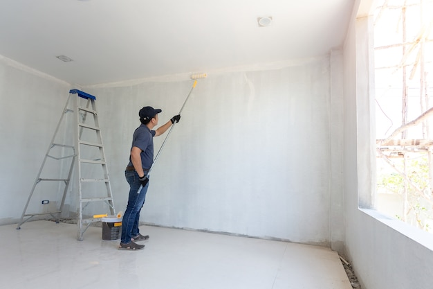 Malermann bei der arbeit mit einer farbenrolle auf der wand