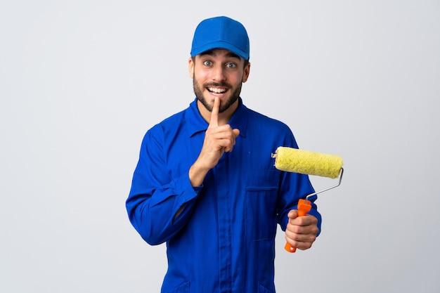 Malermann, der einen farbroller auf weißer wand hält, die ein zeichen der schweigegeste zeigt, die finger in mund setzt