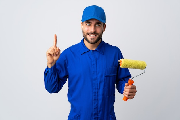 Malermann, der einen farbroller auf weißer wand hält, die eine große idee aufzeigt