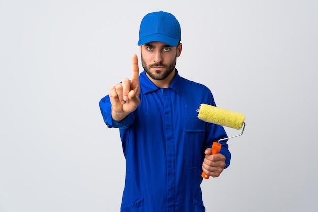 Malermann, der einen farbroller auf weißer wand hält, die einen mit ernstem ausdruck zählt