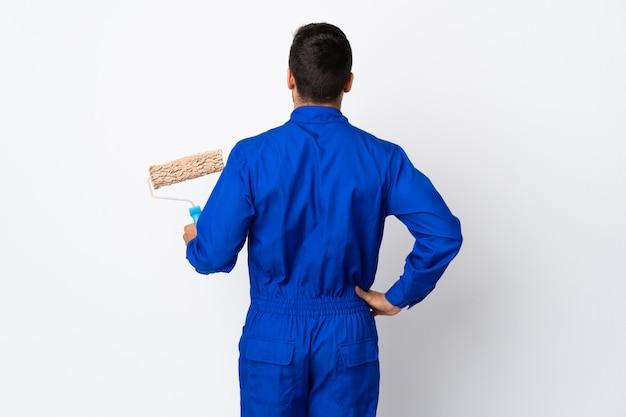 Malermann, der einen farbroller auf weißer wand in der hinteren position hält
