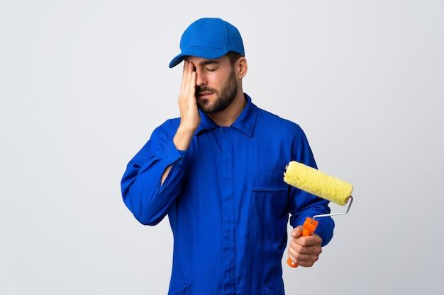 Malermann, der einen farbroller auf weißer wand mit kopfschmerzen hält