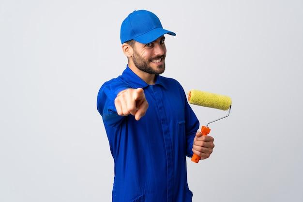 Malermann, der einen farbroller hält, der vorne mit glücklichem ausdruck zeigt