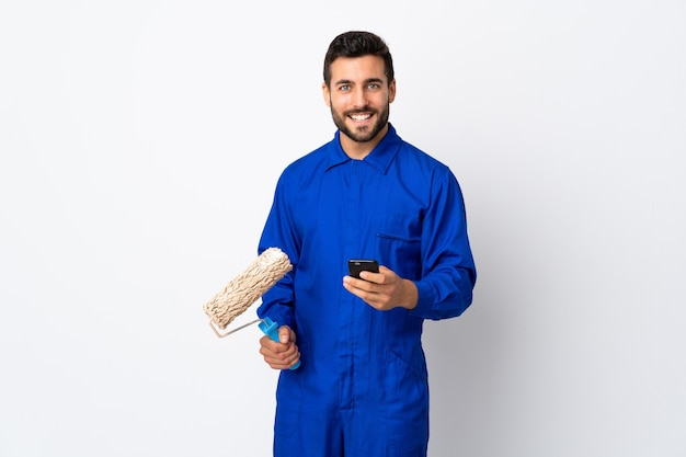 Malermann, der einen farbroller lokalisiert auf weiß hält, der eine nachricht mit dem handy sendet