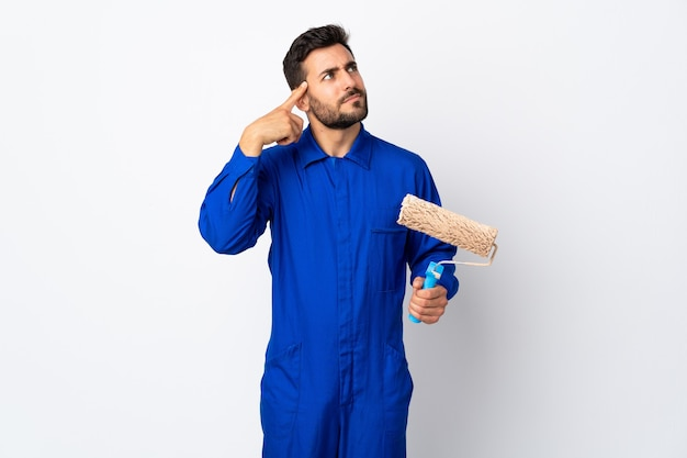 Malermann, der einen farbroller lokalisiert auf weißem hintergrund hält, der die geste des wahnsinns macht, der finger auf den kopf setzt