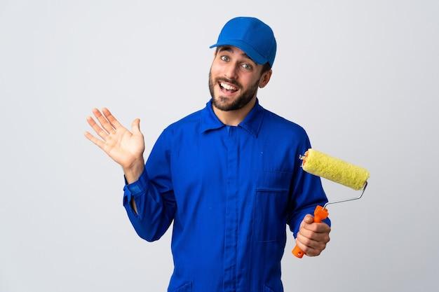 Malermann, der einen farbroller lokalisiert auf weißem hintergrund hält, der mit hand mit glücklichem ausdruck salutiert