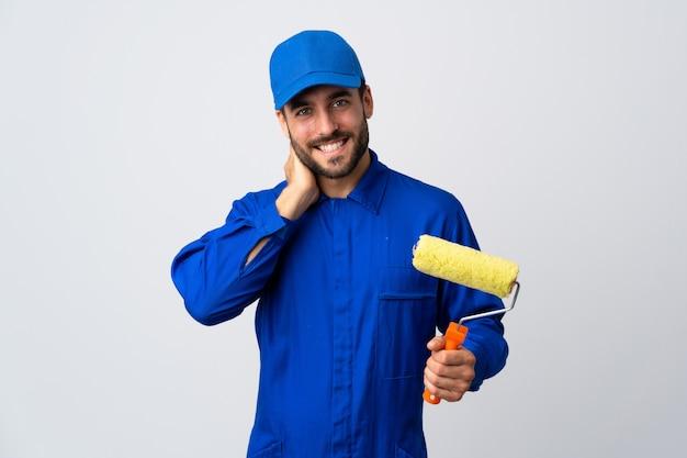 Malermann, der einen farbroller lokalisiert auf weißem wandlachen hält