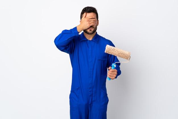 Malermann, der einen farbroller lokalisiert auf weißen wandbedeckungsaugen durch hände hält
