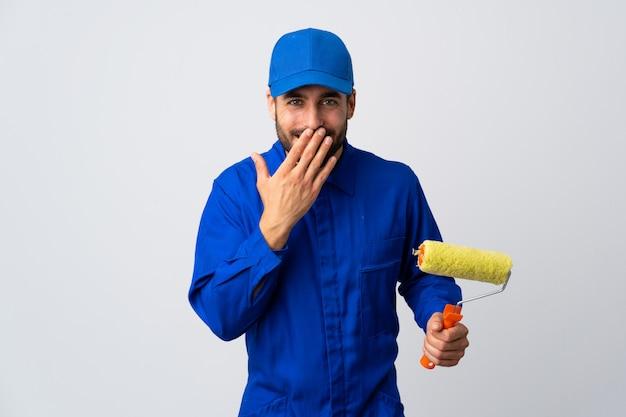 Malermann, der einen farbroller lokalisiert auf weißer wand glücklich und lächelnd hält mund mit hand hält