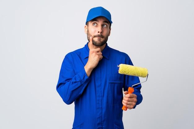 Malermann, der einen farbroller lokalisiert auf weißer wand hält, der zweifel und denken hat