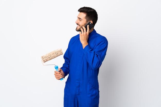 Malermann, der einen farbroller lokalisiert auf weißer wand hält, die ein gespräch mit dem mobiltelefon mit jemandem hält