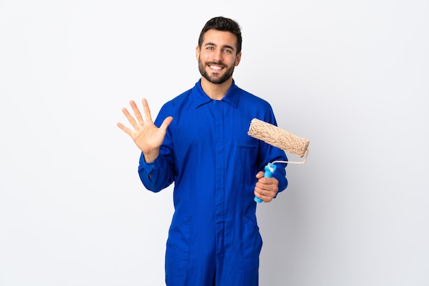 Malermann, der einen farbroller lokalisiert auf weißer wand hält, die fünf mit den fingern zählt