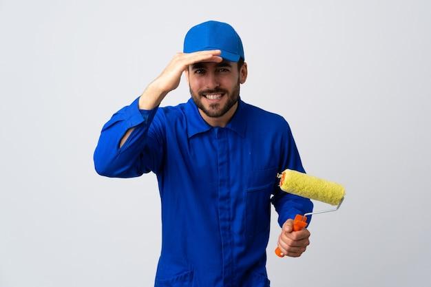 Malermann, der einen farbroller lokalisiert auf weißer wand hält, die weit weg mit hand schaut, um etwas zu schauen