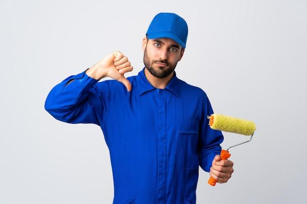Malermann, der einen farbroller lokalisiert auf weißer wand hält, zeigt daumen unten mit negativem ausdruck