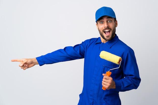 Malermann, der einen farbroller lokalisiert auf weißer wand hält, zeigt finger zur seite und präsentiert ein produkt