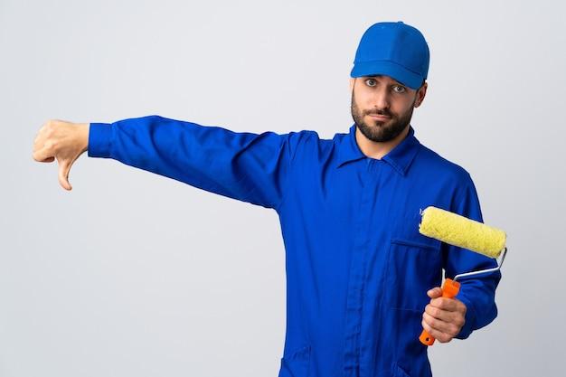 Malermann, der einen farbroller lokalisiert hält, der auf weiß lokalisiert ist, zeigt daumen unten mit negativem ausdruck