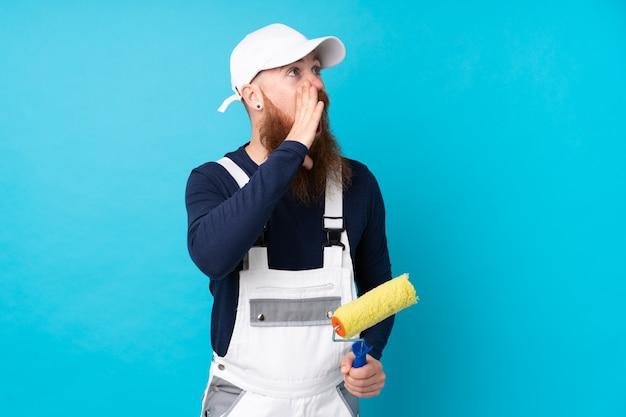 Malermann mit langem bart über der lokalisierten blauen wand, die mit dem breiten mund schreit, öffnen sich