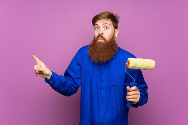 Malermann mit langem bart über lokalisiertem purpurrotem hintergrund zeigend auf die seitenteile, die zweifel haben