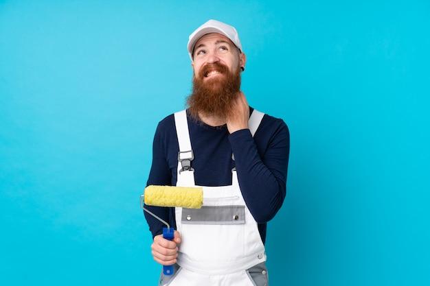 Malermann mit langem bart über lokalisierter blauer wand eine idee denkend