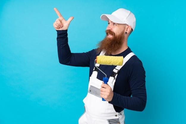 Malermann mit langem bart über lokalisierter blauer wand zeigend mit dem zeigefinger eine großartige idee