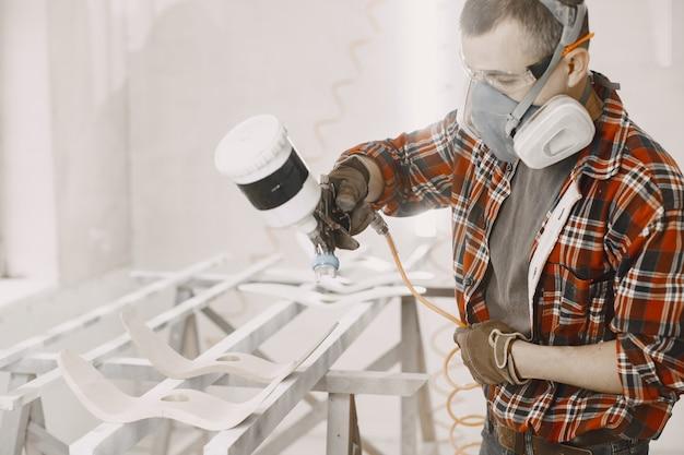 Malermeister in einer fabrik, die holz mit spritzpistole malt