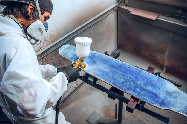 Malermeister in einer fabrik - industrielackierholz mit spritzpistole.