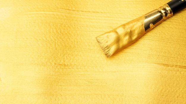 Malerpinsel auf einem goldfarbenen plakataquarell.
