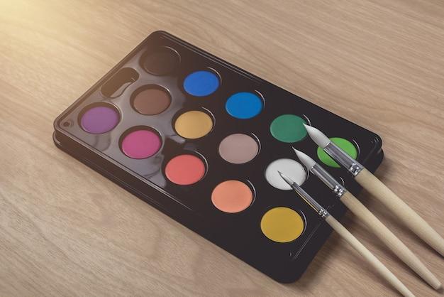 Malerpinsel- und aquarellpalette auf brauner hölzerner tabelle verwendung für künste und bildung