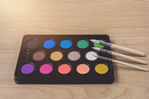 Malerpinsel- und aquarellpalette auf brauner hölzerner tabelle
