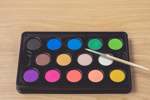 Malerpinsel- und aquarellpalette auf der braunen hölzernen tabelle unter verwendung für künste und bildung