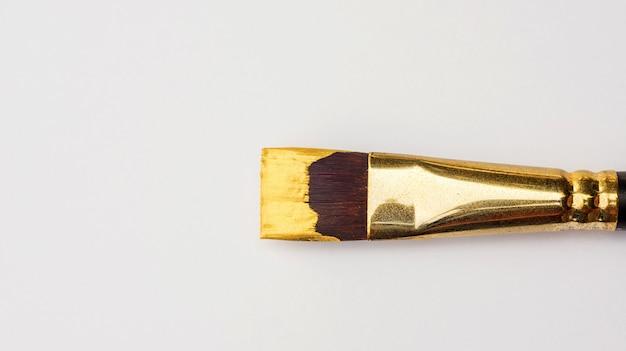Malerpinsel und gold farbiges plakat auf einem weißen hintergrund.